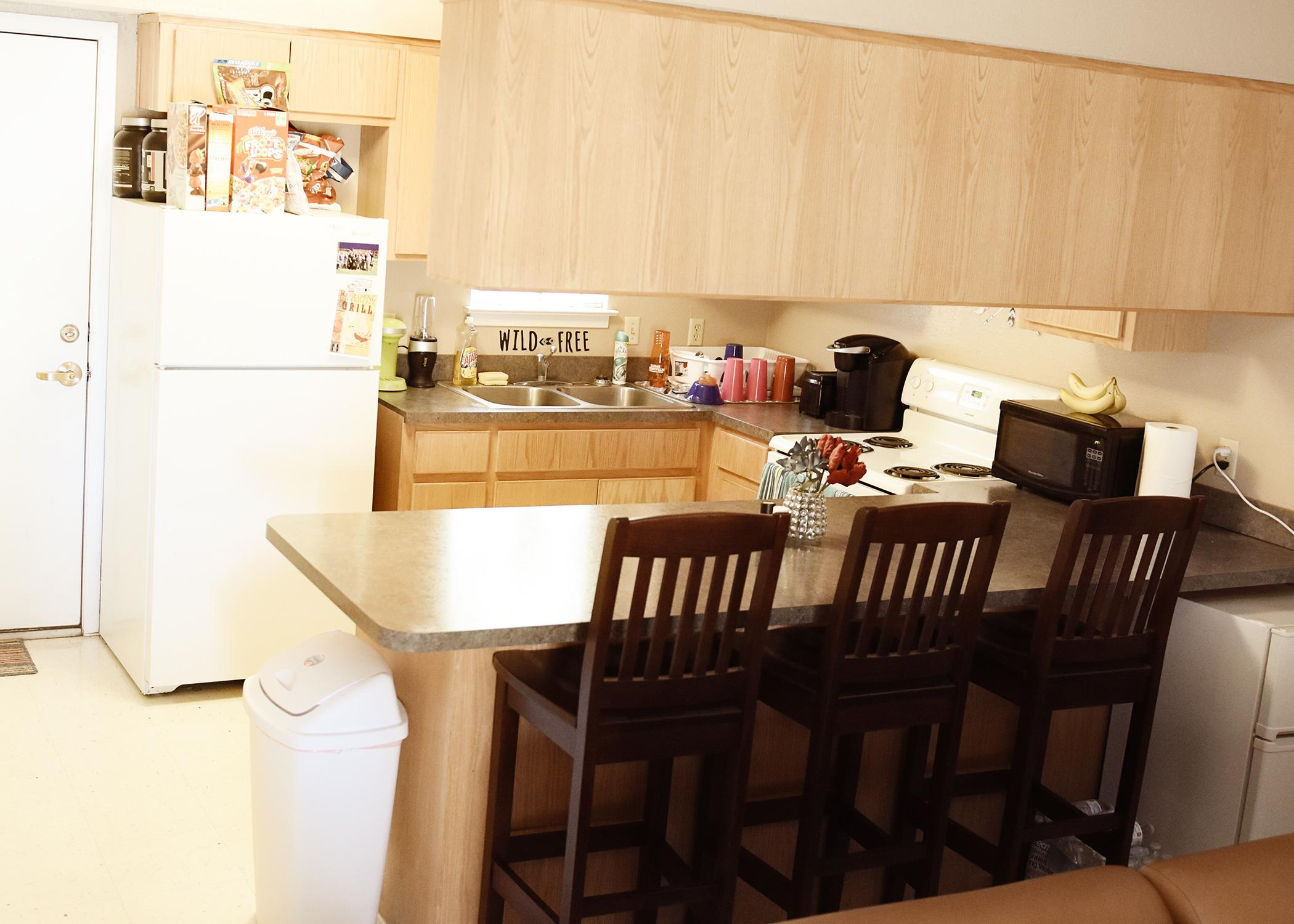The kitchen area has four bar stools, a stove, and a refrigerator.